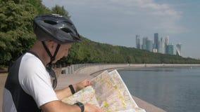 L'uomo in abiti sportivi, casco di riciclaggio, esamina una mappa di carta della città, stock footage
