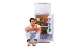 L'uomo accanto al frigorifero in pieno di alimento Fotografia Stock