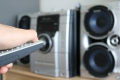 L'uomo accende l'altoparlante stereo di musica facendo uso di telecomando Fotografie Stock Libere da Diritti