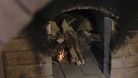 L'uomo accende un fuoco nella stufa del mattone rosso archivi video
