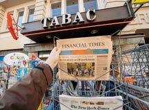 L'uomo acquista dopo un giornale finanziario di periodi dal chiosco della stampa fotografie stock