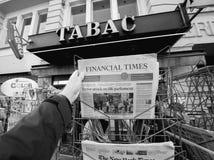 L'uomo acquista dopo un giornale finanziario di periodi dal chiosco della stampa fotografie stock libere da diritti