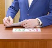 L'uomo ad un seggio elettorale opera la sua scelta fotografia stock