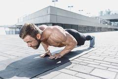 L'uomo adatto di forma fisica che fa la forma fisica si esercita all'aperto alla città Immagine Stock Libera da Diritti