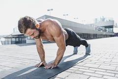 L'uomo adatto di forma fisica che fa la forma fisica si esercita all'aperto alla città Fotografie Stock Libere da Diritti