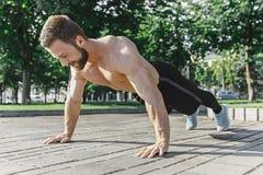 L'uomo adatto di forma fisica che fa la forma fisica si esercita all'aperto alla città Immagini Stock Libere da Diritti