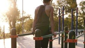 L'uomo adatto e muscolare in camicia è venuto al campo sportivo locale ed addestramento cominciare sulla crociera orizzontale tri archivi video