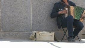 L'uomo adulto abbronzato gioca la fisarmonica all'aperto archivi video