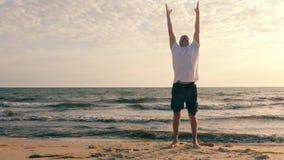L'uomo adulto che fa la respirazione si esercita mentre addestramento di mattina sulla spiaggia del mare archivi video