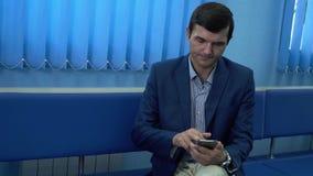 L'uomo adulto che si siede nel corridoio in clinica privata moderna facendo uso dei suoi risultati aspettanti del cellulare della video d archivio