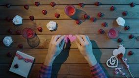 L'uomo adulto con i cuori della carta fatta a mano si siede dalla tavola di legno, vista superiore stock footage