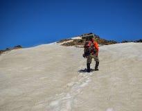 L'uomo adulto con lo zaino scala una montagna nevosa fotografia stock