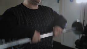 L'uomo adulto con peso in eccesso realizza il sollevamento della barra al mento video d archivio