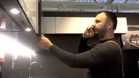 L'uomo adulto con una barba utilizza uno smartphone del telefono cellulare archivi video