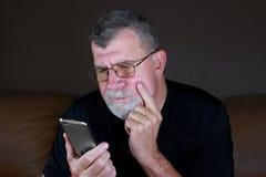 L'uomo adulto contempla il suo telefono cellulare Immagine Stock Libera da Diritti