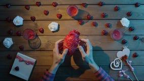 L'uomo adulto esamina il cuore umano di plastica dalla tavola di legno, vista superiore archivi video