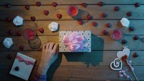 L'uomo adulto mette il biglietto di S. Valentino sulla scatola attuale, vista superiore stock footage