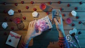 L'uomo adulto mette il denaro contante nel contenitore di regalo come presente di festa, vista superiore video d archivio