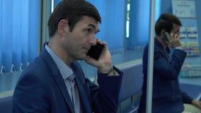 L'uomo adulto nell'usura convenzionale che si siede nel corridoio in clinica privata moderna che parla dal suo cellulare che aspe archivi video