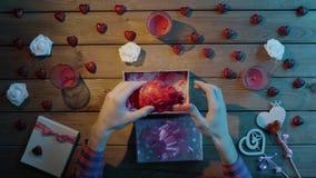 L'uomo adulto ottiene il cuore umano di plastica come presente sconosciuto di festa, vista superiore archivi video