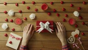 L'uomo adulto ottiene la festa presente in contenitore di regalo sulla tavola di legno, vista superiore archivi video