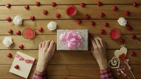 L'uomo adulto ottiene la festa presente in contenitore di regalo sullo scrittorio di legno, vista superiore stock footage