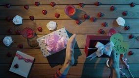 L'uomo adulto prova a capire che cosa si trova dentro i suoi regali di festa e li scuote, vista superiore video d archivio