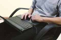 L'uomo adulto si siede e computer portatile di battitura a macchina sulla vostra gamba in Ministero degli Interni Immagine Stock Libera da Diritti