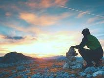 L'uomo adulto solo sta immagazzinando la pietra alla piramide Sommità della montagna delle alpi, uguagliante sole all'orizzonte fotografie stock