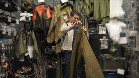L'uomo adulto sta esaminando i pantaloni in un negozio dei vestiti per l'escursione e pescare video d archivio