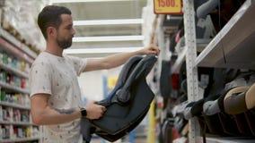 L'uomo adulto sta esaminando una sede di automobile del bambino in negozio, sta girandola e guardando intorno video d archivio