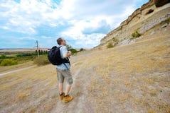 L'uomo adulto sta facendo un'escursione con il suo zaino Fotografia Stock