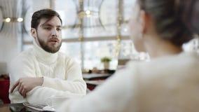 L'uomo adulto sta parlando con donna che tiene la sua mano dalla tavola in un ristorante archivi video