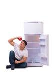L'uomo affamato che cerca soldi per riempire il frigorifero Immagini Stock Libere da Diritti
