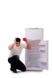 L'uomo affamato che cerca soldi per riempire il frigorifero Fotografia Stock Libera da Diritti