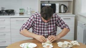 L'uomo affamato sta cucinando lo shawarma sul tavolo da cucina a casa e rapidamente mangia questo video d archivio