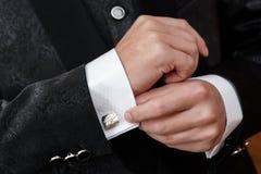 l'uomo afferra un collegamento di polsino su una camicia fotografia stock libera da diritti