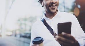 L'uomo africano americano sorridente in cuffia che cammina alla città soleggiata con porta via il caffè e godere di ascoltare mus Immagini Stock Libere da Diritti