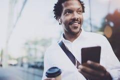 L'uomo africano americano sorridente in cuffia che cammina alla città soleggiata con porta via il caffè e godere di ascoltare mus Fotografia Stock