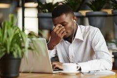 L'uomo africano annoiato ha deciso il problema che lavora al caffè Fotografie Stock Libere da Diritti