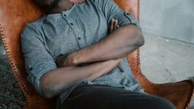 L'uomo africano bello con la barba sta sedendosi nella sedia e nel sorridere Un maschio sembra vago, premuroso e calmo Fotografie Stock