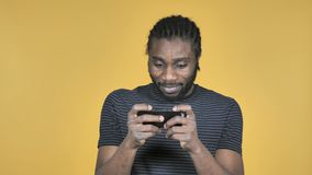 L'uomo africano casuale che gioca il gioco su Smartphone ha isolato su fondo giallo archivi video