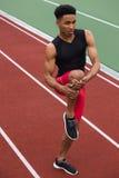 L'uomo africano dell'atleta fa l'allungamento degli esercizi sulla pista corrente Fotografia Stock