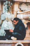 L'uomo africano si siede sotto il computer portatile BO del lavoro della fontana di Nettuno immagini stock libere da diritti