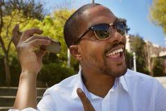 L'uomo africano sorridente felice in camicia bianca ascolta messaggio sano sul telefono cellulare mentre si siede all'aperto Immagini Stock
