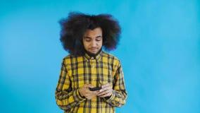 L'uomo afroamericano con capelli ricci sta pensando prima invia il messaggio su fondo blu Concetto delle emozioni video d archivio