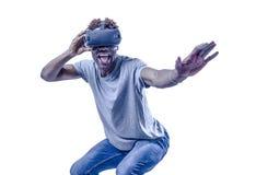 L'uomo afroamericano eccitato giovane attivo che gode del gioco felice con dispositivo di realtà virtuale degli occhiali di prote immagine stock