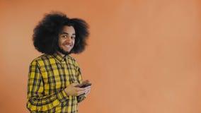L'uomo afroamericano ha ricevuto un nuovo messaggio sul suo telefono su fondo arancio Concetto delle emozioni video d archivio
