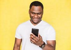 L'uomo afroamericano soddisfatto tiene lo smartphone, fissa con l'espressione felice immagini stock