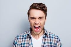 L'uomo aggressivo in camicia a quadretti con la bocca spalancata è da fotografie stock libere da diritti